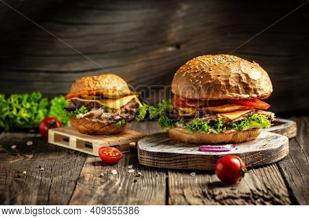 Tasty Grilled Homemade Burgers With Beef, Tomato, Cheese, Bacon And Lettuce On Rustic Wooden Backgro