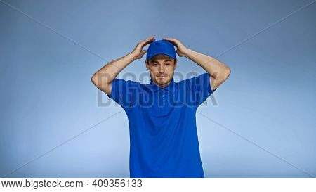 Discouraged Delivery Man Holding Hands Over Head Isolated On Blue.