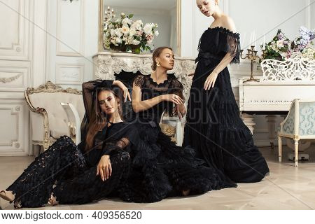 Three Young Pretty Lady In Black Lace Fashion Style Dress Posing In Rich Interior Of Royal Hotel Roo