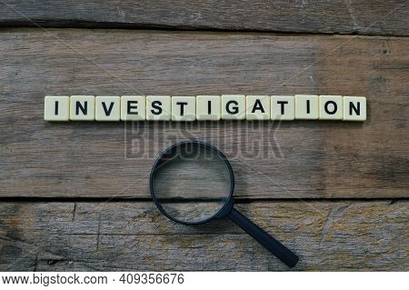 Top View Of Magnifying Glass And Square Letters With Text Investigation.
