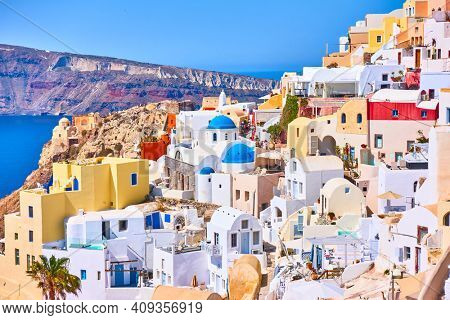 View of houses of different colours on the sea coast in Oia (Ia) town in Santorini island, Greece. Picturesque greek landscape