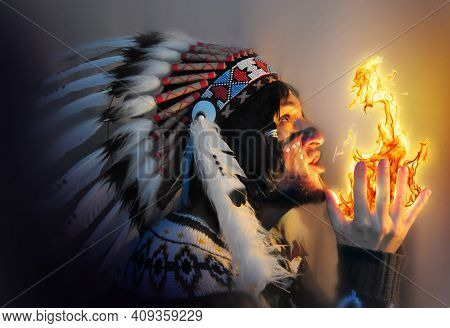 Portrait Of A Young Handsome Guy In A Hat With A Feather Of The Chief Of The Indians. Fire And Man -