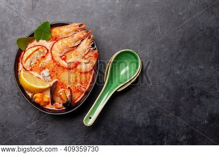 Traditional Thai soup Tom Yum kung with seafood, coconut milk and chili pepper. Top view flat lay with copy space