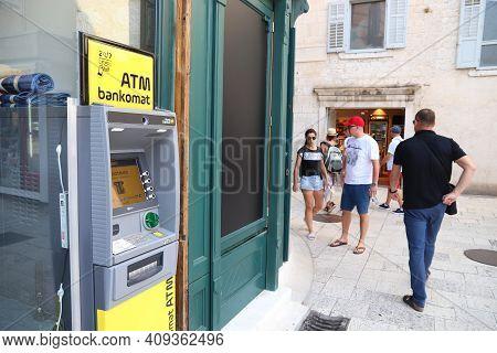 Split, Croatia - July 20, 2019: Tourists Walk By Atm Banking Machine In Split. Croatia Had 18.4 Mill