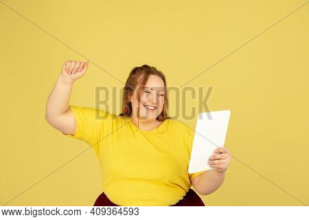 Using Tablet. Beautiful Plump Caucasian Plus Size Model Isolated On Yellow Studio Background. Concep