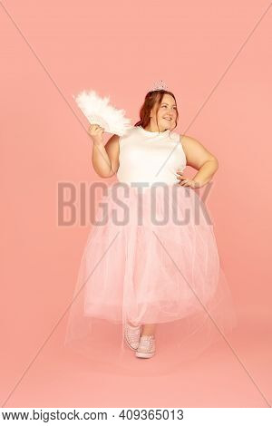 Beautiful Plump Caucasian Plus Size Model In Fairys Outfit Isolated On Pink Studio Background. Conce