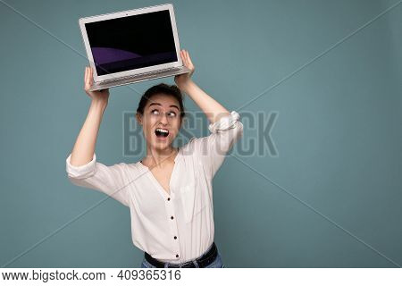Beautiful Young Woman Holding Netbook Computer Looking Up And Saying Wow Wearing White Shirt Isolate