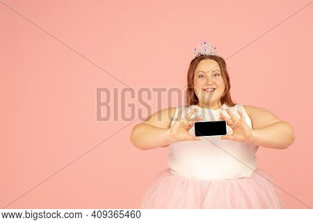 Shows Screen. Beautiful Plump Caucasian Plus Size Model In Fairys Outfit On Pink Studio Background.