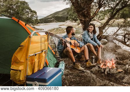 Romantic Couple Sitting By Bonfire. Beautiful Couple In Love Enjoying At Campsite.