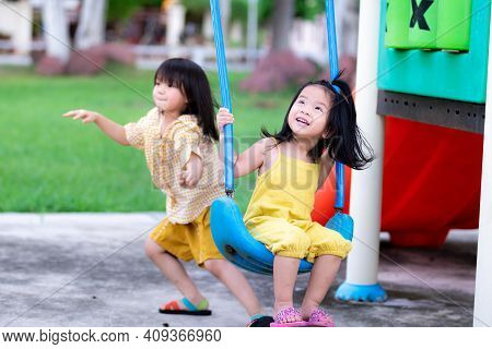 Sisters Play Happy Swings. Older Sister Swing And Run To The Side. Brethren Play Together On The Pla