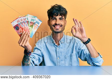 Young hispanic man holding swiss franc banknotes sitting on the table doing ok sign with fingers, smiling friendly gesturing excellent symbol