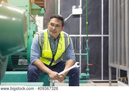 Portrait Of Worker Or Technician Man Hold Wrench, Smile And Stand At Generator Room