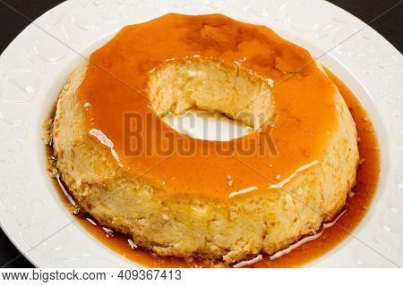 An Eggs Flan On A White Ceramic Plate On A Black Background In A Top View