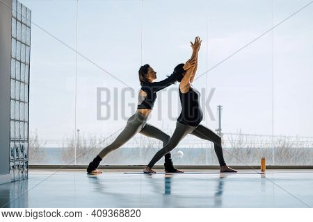Young Female Yoga Instructor Teaching Yoga In Studio To A Pregnant Woman. Prenatal Practice, Working