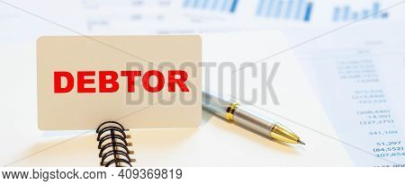 Debtor - Financial Text On Notepad With Pen With Blurred Financial Indicators