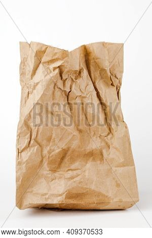 Crumpled Paper Bag With Greasy Spots On A White Isolated Background. Recycling Of Secondary Waste.