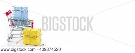 Cart With A Box Of Gifts On A White Background. Holiday And Shopping Concept. Selective Focus. Banne
