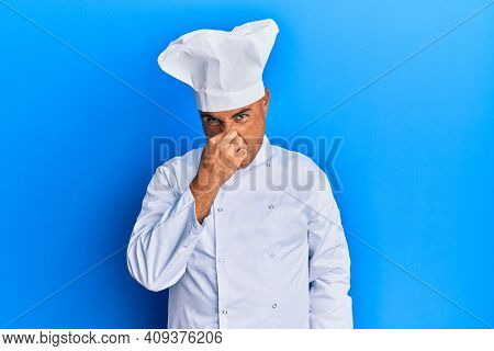 Mature middle east man wearing professional cook uniform and hat smelling something stinky and disgusting, intolerable smell, holding breath with fingers on nose. bad smell