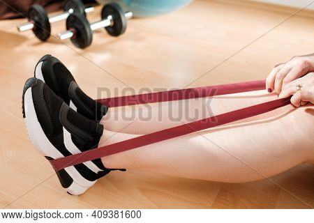 Close Up Female Legs In Sneakers Doing Exercises With Fitness Elastic Bands At Home During Lockdown.