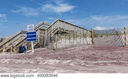 Wooden Staircase For Walkway Over The Sand Dunes On A Fire Islands Beach With Signs Reading Alcohol