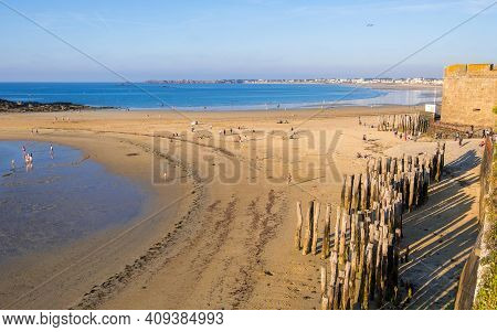 Saint-malo, France - August 25, 2019: Beach In The Evening Sun And Wooden Breakwater Poles Outside T
