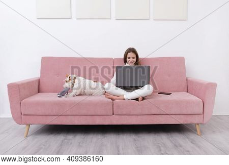1 White Teenage Girl 10 Years Old In A White Sweater And Jeans Sits On A Pink Sofa With A Laptop, A