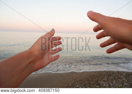 Hands Reaches For The Sunset Against The Background Of The Sea. Silhouette Of A Hand In Front Of Sun