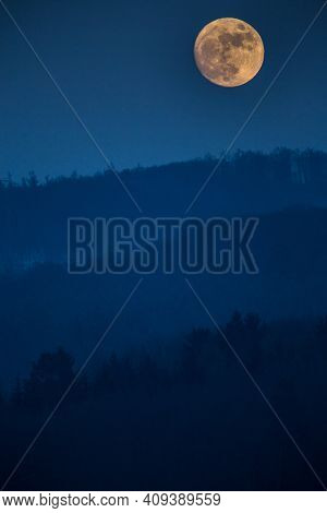 Atmospheric moon landscape of twilight in mountains. Dark lilac sky and big moon with cloud above silhouettes of mountain forests at dusk