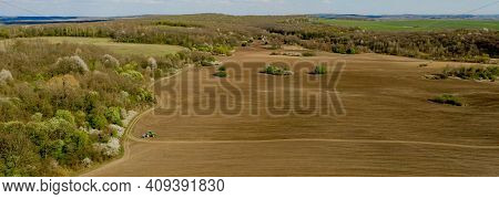 Aerial View Large Tractor Cultivating A Dry Field. Top Down Aerial View Tractor Cultivating Ground A