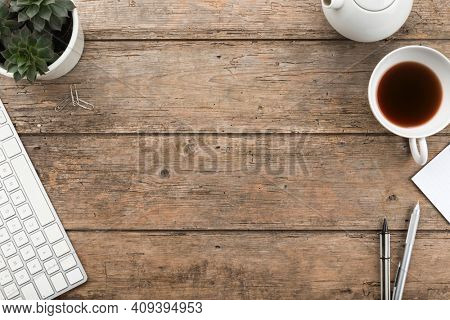Flat lay Rustic wooden home office desk background with teapot, tea cup, sempervivum houseplant, pens and copy space