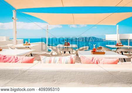Greece, Santorini. Restaurant With Tables In Seafront Of Aegean Sea On Santorini Cyclades Island Wit