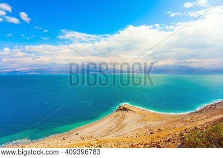 The smooth surface of the very salty sea water reflects the sky and clouds. Low winter clouds are reflected in the green sea water. Israel. Legendary Dead Sea.