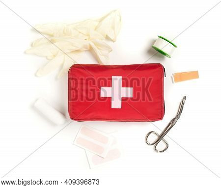 Red First Aid Medical Kit Bag With Scissors, Tape And Gloves Top View Flat Lay From Above Over White