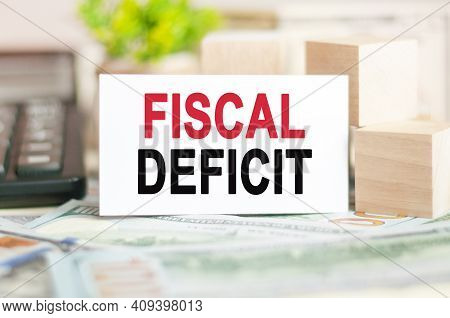 The Words Fiscal Deficit Is Written On White Paper Card Near A Wooden Cubes, Banknotes, Black Calcul