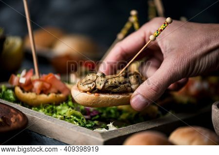 a young caucasian man takes a vegan spanish pincho from a tray with some other pinchos, made with bread with different toppings, served as snacks or appetizers