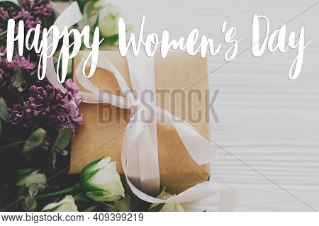 Happy Women's Day Text Sign On Stylish Gift Box With Lilac And Roses Flowers On White Wood. 8 March