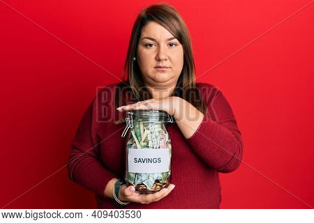 Beautiful brunette plus size woman holding jar with savings relaxed with serious expression on face. simple and natural looking at the camera.
