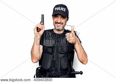 Middle age handsome policeman wearing police uniform and bulletproof vest holding gun smiling happy and positive, thumb up doing excellent and approval sign