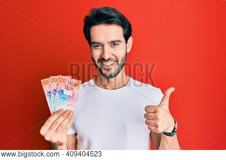 Young hispanic man holding swiss franc banknotes smiling happy and positive, thumb up doing excellent and approval sign