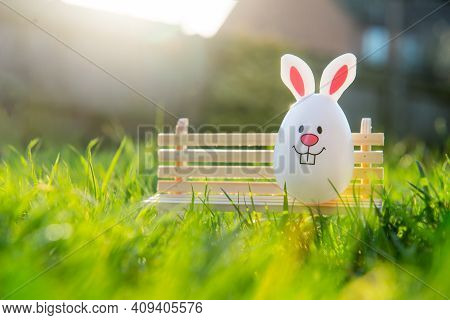Creative Easter Composition Of Funny Easter Egg With Bunny Ears Sitting On A Miniature Bench On Gree
