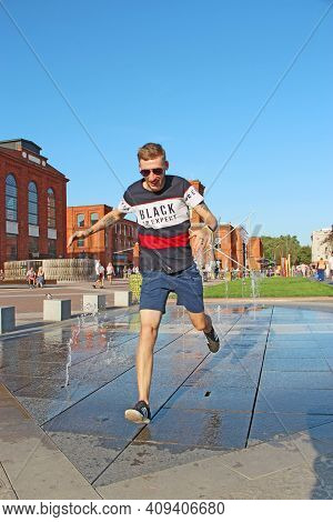 Lodz - Poland. 05 August 2019: Fashionable Guy Running Through Puddle Near Fountains. Summer Fun Of