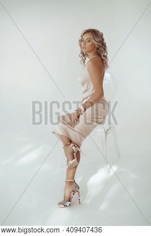 Portrait Of Beautiful Young Girl Is In A Fashionable Dress On A White Background