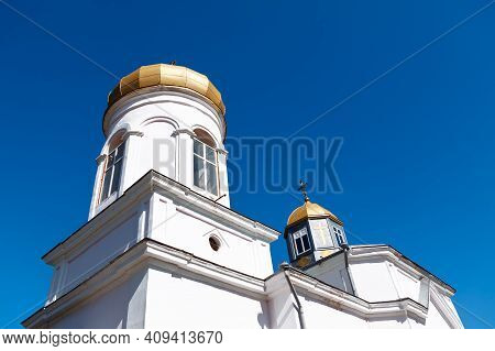 White Monastery Against Blue Sky . Place Of Worship With Golden Dome