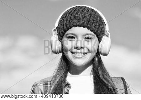 Pprotect Your Childs Ears. Happy Girl Wear Ear Phones On Sunny Blue Sky. Little Kid Listen To Music