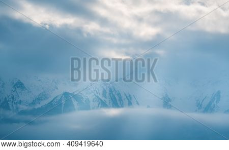Mountain Peaks Covered With Snow Between Fog Clouds With Bright Sunrays Shining Through, Mieminger P