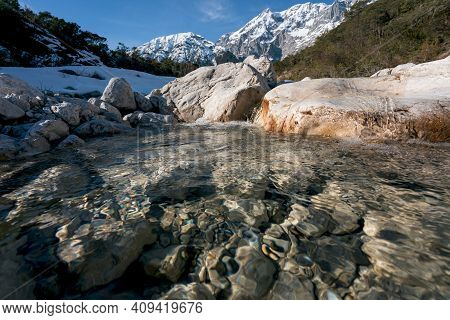 Wild Clear Mountain River Flowing Over Rocks Through Evergreen Forest With Last Snow, Mieminger Plat