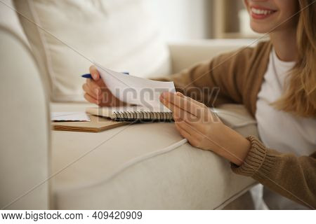Happy Woman Writing Letter On Sofa At Home, Closeup