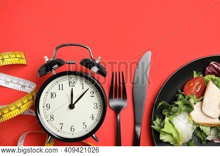 Plate Of Tasty Salad, Cutlery, Alarm Clock And Measuring Tape On Red Background, Flat Lay. Nutrition