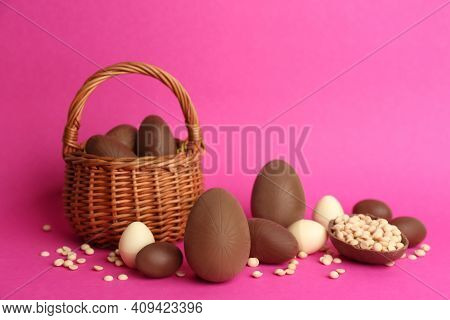 Sweet Chocolate Eggs And Wicker Basket On Pink Background