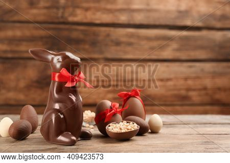 Chocolate Easter Bunny With Red Bow And Eggs On Wooden Table. Space For Text